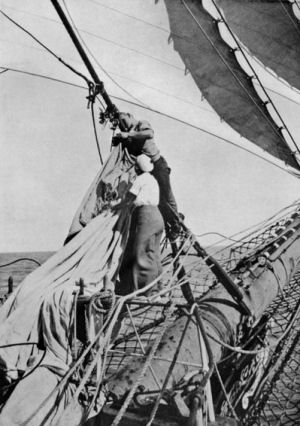 picture of two sailors - one female - changing the jib sail